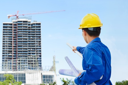 civil engineer: Male contractor or civil engineer looking at the bulding project on progress Stock Photo