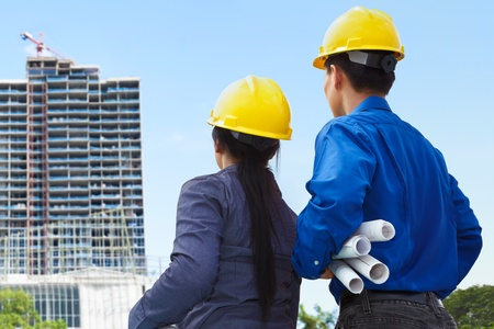 Two contractors, man and woman facing the building project in progress photo