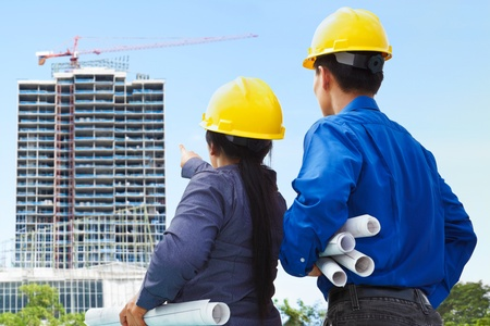woman engineer: Two contractors, man and woman facing the building project in progress