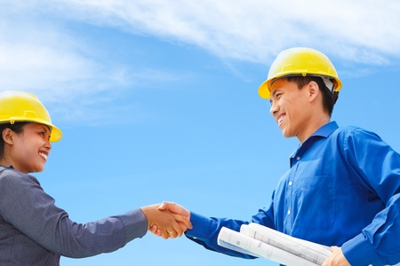 Two contractors shake hands with blue sky background photo