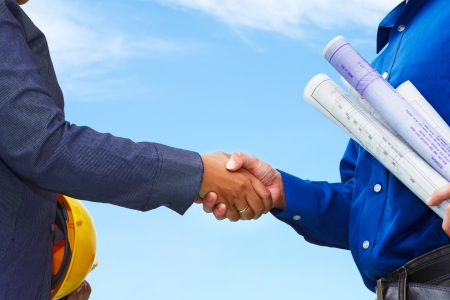 female engineer: Two contractors shake hands with blue sky background