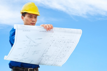 Contractor holding blueprint with blue sky background photo