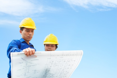 south east asian: Contractor holding blueprint with blue sky background