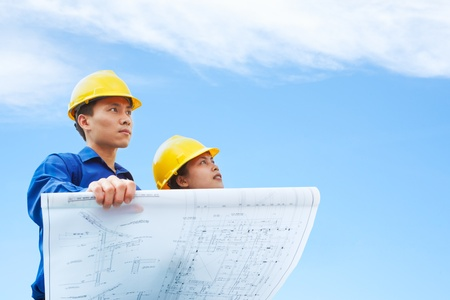 female engineer: Contractor holding blueprint with blue sky background