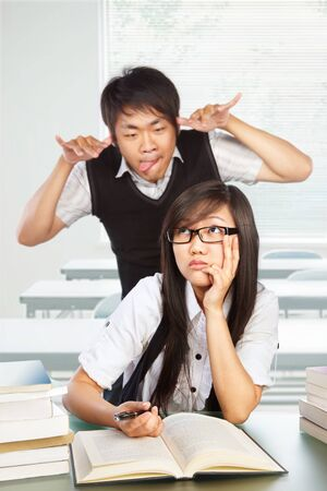naughty boy: male student mocking and bothering the female student in class