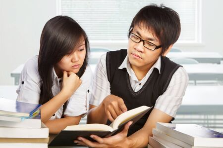 Male and female student studying together in the classroom