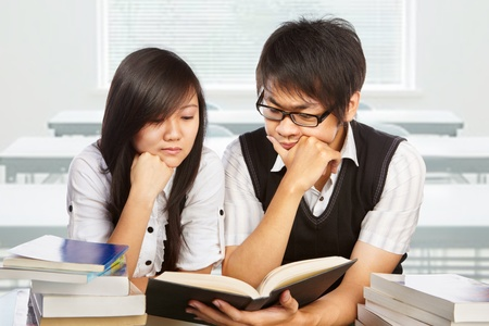 Male and female student studying together in the classroom photo
