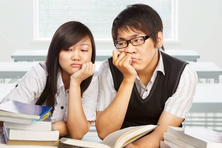 Two stressfull students looking away to the books in the classroom photo