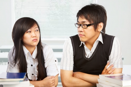 Male and female student looking each other full of hatred photo