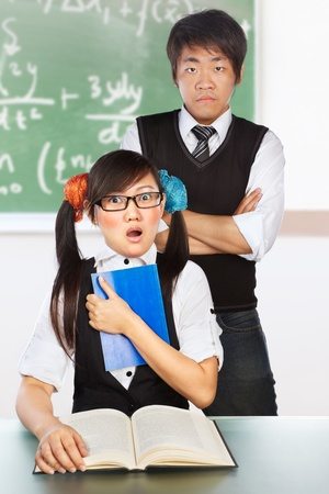 Male tutor teaching the nerd female student in classroom photo