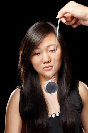 Young Chinese lady being hypnotized with pendulum photo