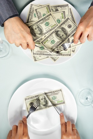 People hand eating the dollar bills on the plate Stock Photo