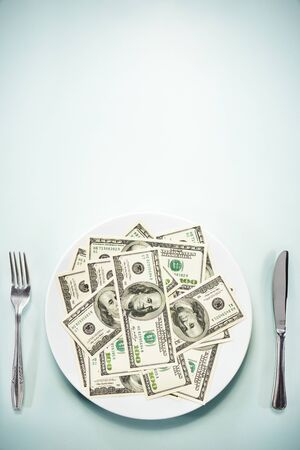 US $ 100 bills on the plate, setting on the glass table photo