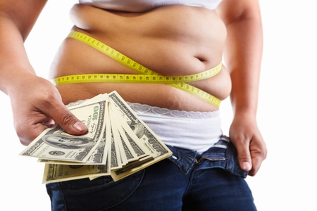 Overweight female stomach strapped with measuring tap and lots of 100 dollar bills