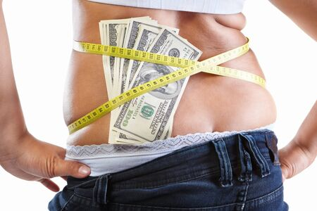 strapped: Overweight female stomach strapped with measuring tap and lots of 100 dollar bills