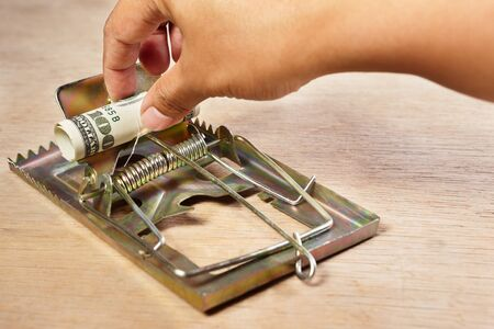 taking a risk: People hand is about to catch the money placed on mousetrap