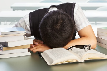 Male college student fall asleep on the table photo