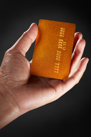 Hand holding a golden credit card, against dark background. Name and number on card has been altered photo