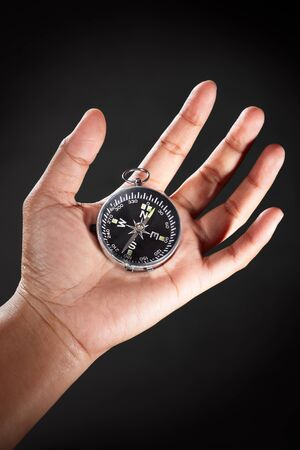 Hand holding a compass, against dark background photo