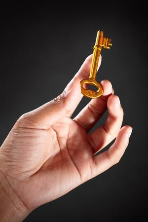 hand key: Hand holding a golden key, against dark background