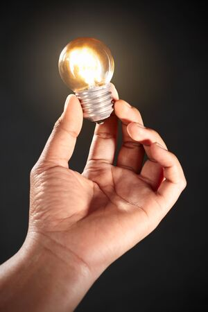 Hand holding a bright light bulb, , against dark background photo