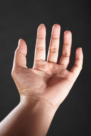 facing the camera: Palm facing camera, like holding something, against dark background Stock Photo