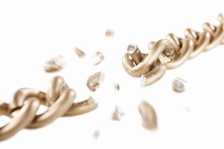 broken link: Broken link di catena d'oro con il movimento sfocato dei pezzi sparsi, isolati su sfondo bianco. profondit� di campo Archivio Fotografico