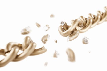 Broken link of golden chain with blurry movement of the scattered pieces, isolated against white background. small depth of field Stock Photo - 10801973