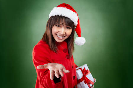Asian lady with red Christmas outfit holding a present photo