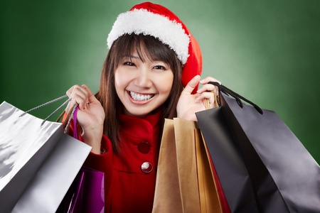 Asian lady with red Christmas outfit holding lots of shopping bags photo