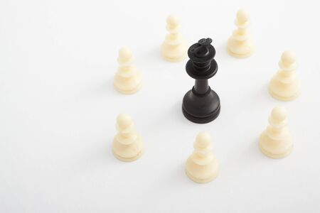 King pieces standing surrounded by other color chess pieces photo