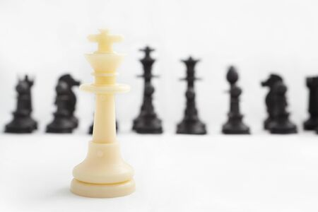 all in one: One piece of white chess (king) against all the other side (black ones) Stock Photo