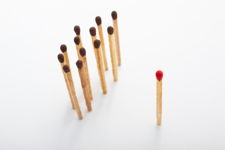 racism: Red tip matches standing alone and on the other side a group of brown tip matches