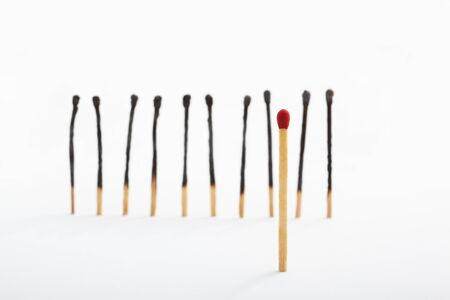 majority: Red tip matches standing alone and on the other side a group of burnt matches