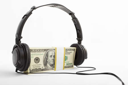 news values: A stack of US$100 bills with headphone put on, over white background