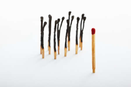 burnt wood: Red tip matches standing alone and on the other side a group of burnt matches