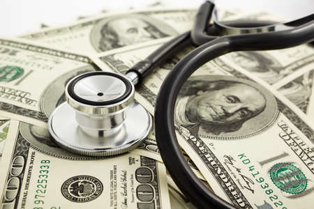 A stethoscope on pile of dollar bills photo
