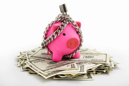 shut down: Chained pink piggy bank on pile of dollars over white background
