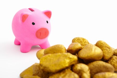 Pink piggy bank and pile of gold rocks over white background photo