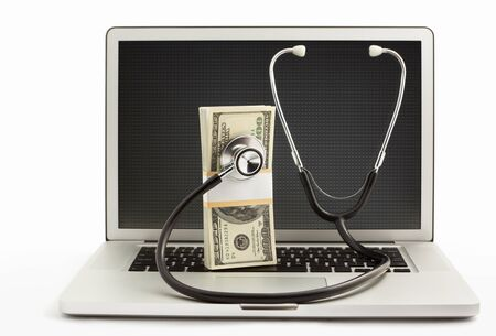 Stack of dollar bills with stethoscope being checked by the laptop over white background photo
