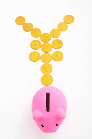 yen sign: Pink piggy bank and yen sign made from gold coins over white background