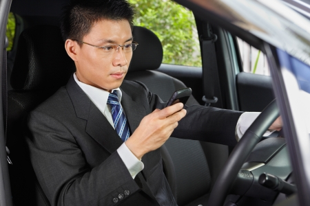 Chinese businessman inside car texting on his cell phone