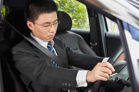 Chinese businessman inside car falling asleep Standard-Bild