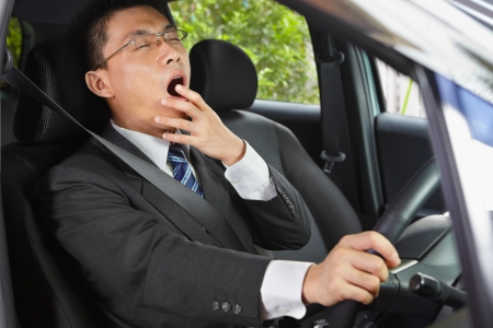 Chinese businessman inside car yawning while driving