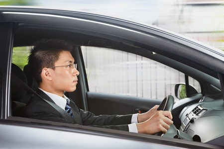 Chinese businessman driving a car looking to the front