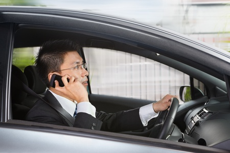 Chinese businessman inside car talking on cell phone while driving photo