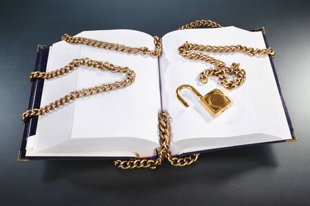 lock and chain: A hard cover book open showing blank page with golden chain and lock