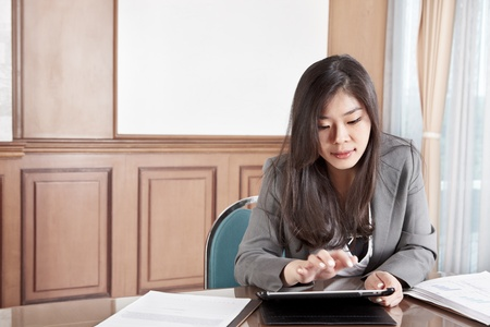 Chinese busineswoman busy with her tablet in the office Stock Photo - 12751431