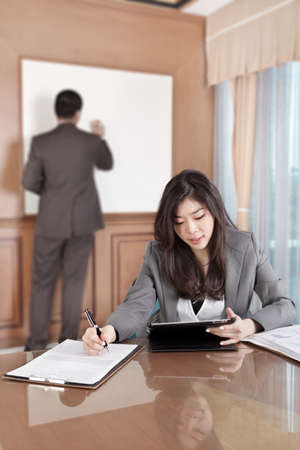 Chinese businesswoman busy working with her tablet while businessman on background busy preparing presentation photo