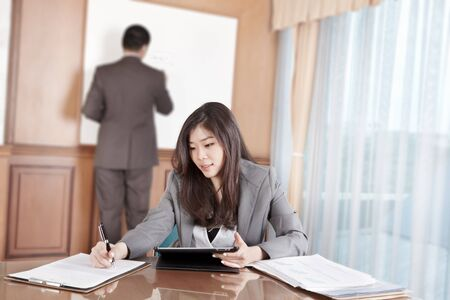 Chinese businesswoman busy working with her tablet while businessman on background busy preparing presentation
